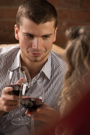 Couple toasting wine glasses while sitting at restaurant and having romantic date photo