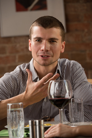 Man having fun at restaurant while drinking red wine and chatting with friends Stock Photo