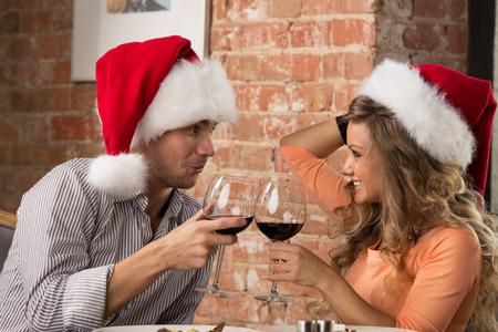 Couple toasting wine glasses at restaurant while celebrating Christmas photo