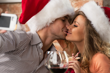 Young happy couple wearing Santa hats looking at one another in restaurant, kissing and taking photos of themselves on mobile phone camera while celebrating Christmas photo