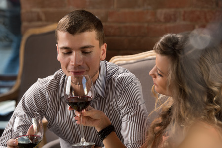 Young happy couple having romantic date at restaurant - drinking wine and eating gourmet food photo