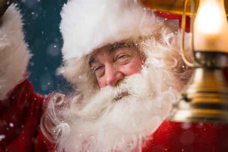 sneaking: Santa Claus is holding a shining lantern while sneaking to his home outdoors at North Pole  Stock Photo