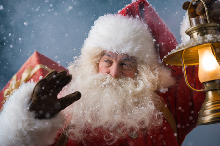 finds: Photo of happy Santa Claus outdoors in snowfall lights the way with vintage lantern while carrying gifts to children