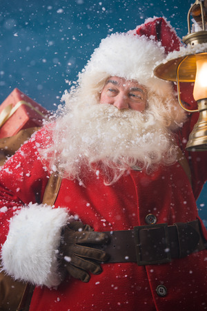 sneaks: Photo of happy Santa Claus outdoors in snowfall lights the way with vintage lantern while carrying gifts to children