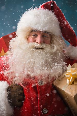 hombre con sombrero: Santa Claus caminando sobre la nieve con su saco de un mont�n de regalos. Noche de invierno con las nevadas