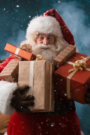 Kerstman lopen op de sneeuw met zijn zak van veel cadeautjes. Winter nacht met sneeuwval