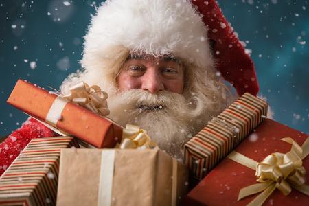 Santa Claus wandelen in de sneeuw met zijn zak met veel cadeautjes. Winter nacht met sneeuwval Stockfoto