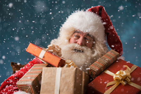 Santa Claus walking on the snow with his sack of lots of presents. Winter night with snowfall