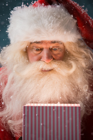 north pole: Happy Santa Claus opening his Christmas gift at North Pole Stock Photo