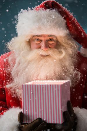 Portret van de gelukkige Kerstman opening geschenkdoos buiten op Noordpool. Magische licht van doos op zijn gezicht Stockfoto