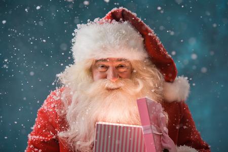 Happy Santa Claus opening zijn kerstcadeau op North Pole