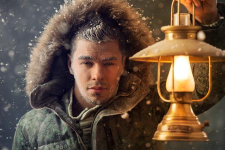 Brutal man walking under snowstorm at night lighting his way with lantern photo