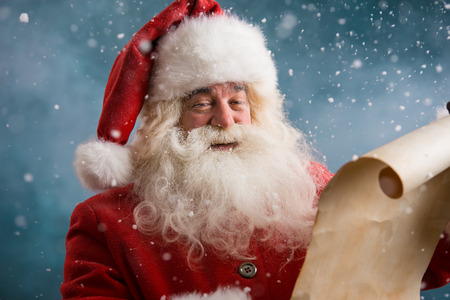 to the north: Portrait of happy Santa Claus reading Christmas letter outdoors at north pole at snowfall Stock Photo