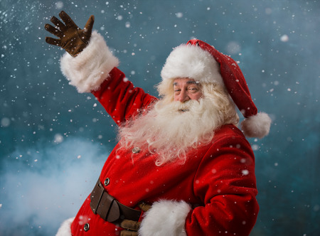 Santa Claus welcoming to the North Pole standing outdoors in snowfall Stock Photo