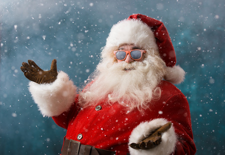 to santa: Santa Claus wearing sunglasses dancing outdoors at North Pole in snowfall. He is celebrating Christmas after hard work