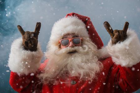 Santa Claus mit Sonnenbrille tanzen im Freien in North Pole in Schneefall. Er feiert Weihnachten nach harter Arbeit Standard-Bild - 31531680