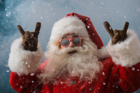 fun: Santa Claus wearing sunglasses dancing outdoors at North Pole in snowfall. He is celebrating Christmas after hard work
