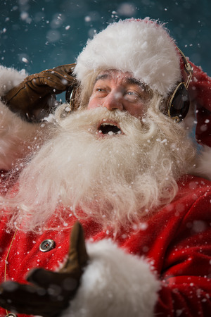 Santa Claus is luisteren naar muziek in hoofdtelefoons buitenshuis op Noordpool, plezier hebben tijdens het leveren van geschenken Stockfoto