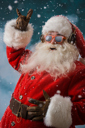 Santa Claus is listening to music in headphones outdoors at North Pole, Having fun while delivering gifts Stock Photo