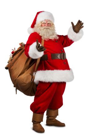 santa claus�: Real Santa Claus llevando gran bolsa llena de regalos, aislado en fondo blanco Foto de archivo