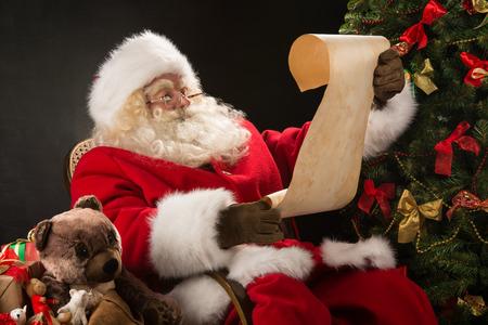 Portret van gelukkige zitting van de Kerstman op zijn kamer thuis in de buurt van de kerstboom en een grote zak en het lezen van Kerstmis brief of wenslijstje Stockfoto