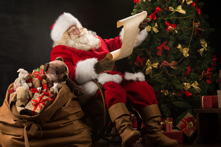 adult toys: Portrait of happy Santa Claus sitting at his room at home near Christmas tree and big sack and reading Christmas letter or wish list