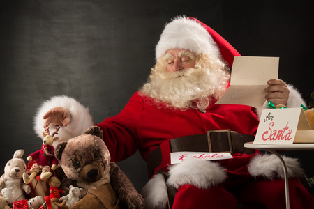 Santa Claus sitting at home at comfortable armchair holding envelope and reading childrens letters and wishes and choosing toys from big sack near him.  photo
