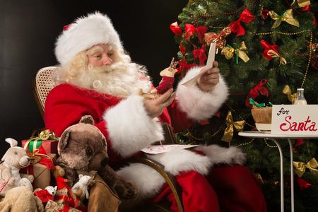 Kerstman zit thuis op een comfortabele fauteuil met envelop en leest brieven en wensen van kinderen en het kiezen van speelgoed uit grote zak in de buurt van hem.