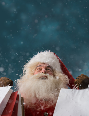Photo of happy Santa Claus outdoors in snowfall holding shopping bags and looking upwards on big copyspace. Christmas sales and discount concept