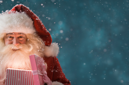 santa: Portrait of happy Santa Claus opening gift box outdoors at North Pole. Magical light from box on his face