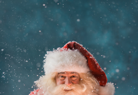 Magical portrait of Santa Claus in snowfall at North Pole. Lots of copyspace
