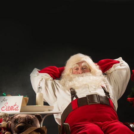 Santa Claus keeping his hands behind head while relaxing at home sitting in comfortable armchair near christmas tree drinking milk and eating fresh cookies. For Santa sin on table Stock Photo