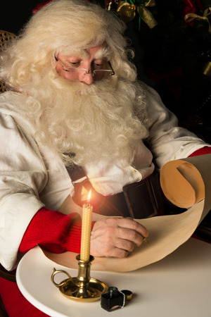 Santa Claus sitting at home and writing on old paper roll to do list with quill pen and ink at night with candle light. Authentic vintage style portrait. photo