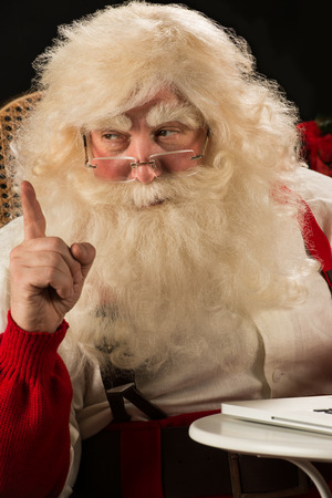 Santa Claus working on computer and having great idea. Idea gesture photo