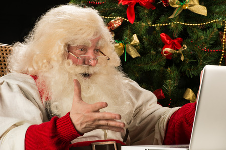 Santa Claus using laptop at home against Christmas Tree and is really impressed photo