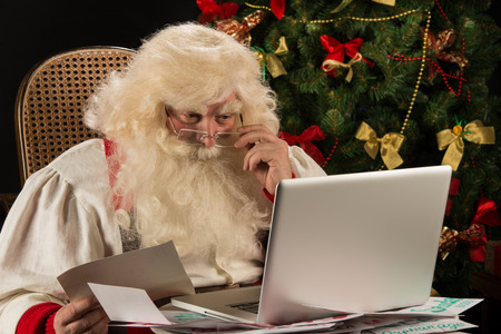 Santa Claus working on computer reading emails and paper letters from children from all over the world photo