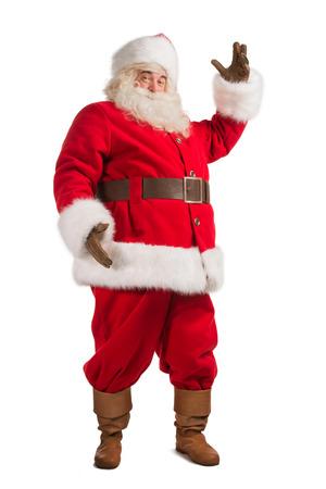 Kerstman gebaren zijn hand geïsoleerd op een witte achtergrond. Presenteren iets. Volledige lengte portret Stockfoto