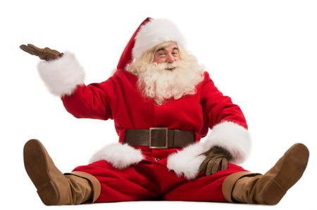 Hilarische en grappige kerstman blijkt presenteren gebaar terwijl het zitten op een witte achtergrond volledige lengte