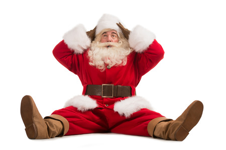 to santa: Hilarious and funny Santa Claus confused while sitting on a white background full length