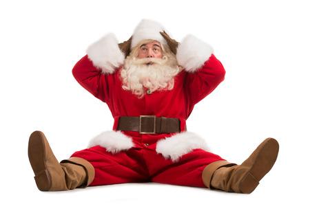 Hilarische en grappige Kerstman verward terwijl het zitten op een witte achtergrond volledige lengte Stockfoto