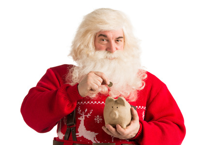 christmas budget: Authentic Santa Claus holding piggy bank and putting golden coin inside, Christmas budget concept