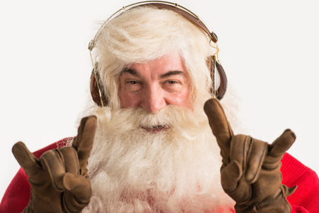 Santa Claus listening to the music with a pair of headphones Stock Photo