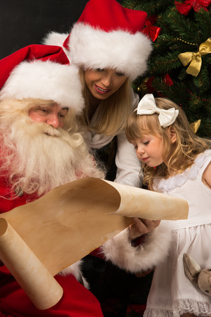 Santa Claus sitting at home with cute little girl and her mother and reading letter photo