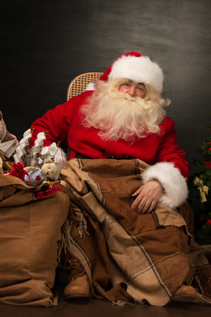 Santa Claus with a huge bag full of Christmas presents sitting in a comfortable chair near the Christmas tree at home photo