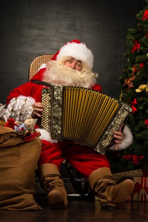 Santa Claus sitting in armchair near Christmas Tree at home and playing music on accordion photo