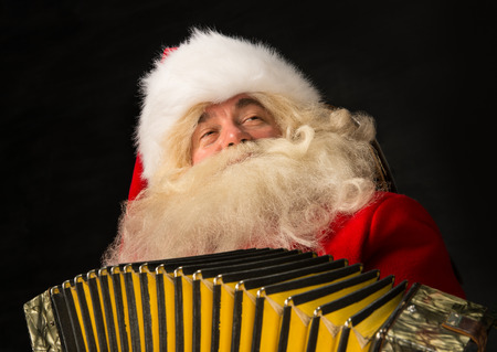 merriment: Santa Claus sitting in armchair at home and playing music on accordion. Christmas party merriment Stock Photo