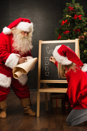 wishlist: Santa Claus with his helper standing near chalkboard with wishlist sign and blank copy space for checkboxes and your text.  Stock Photo