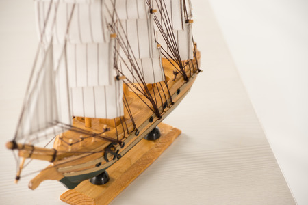 embark: Wooden ship toy model on white table against white background Stock Photo