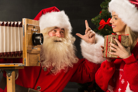 taking a wife: Photo of Santa Claus with his wife taking pictures with Christmas gift at home Stock Photo
