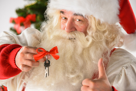 Santa Claus holding keys of new house or apartment and thumbs up, standing near Christmas tree. Good mortgage offer concept